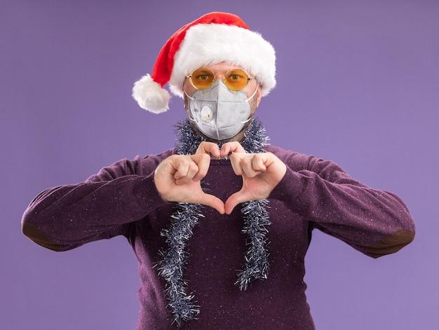 サンタの帽子と保護マスクを身に着けている中年の男性は、紫色の壁に隔離されたハートサインをしている眼鏡と首の周りに見掛け倒しの花輪