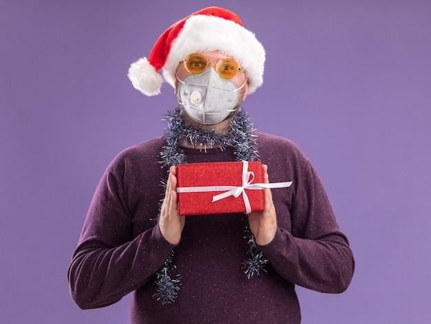 サンタの帽子と保護マスクを身に着けている中年の男性は、紫色の壁に隔離されたギフトパッケージを保持しているメガネと首の周りに見掛け倒しの花輪