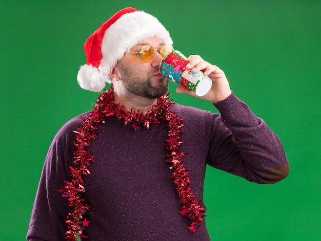 카메라를 마시는 커피를보고 안경 목에 산타 모자와 반짝이 갈 랜드를 입고 중년 남자