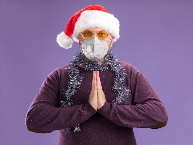 Uomo di mezza età che indossa un cappello da babbo natale e una ghirlanda di orpelli intorno al collo con occhiali e maschera protettiva che tengono le mani insieme isolate sulla parete viola