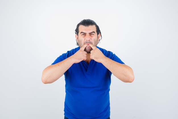 Middle aged man whistling in polo t-shirt and looking angry front view