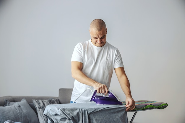 A middle-aged man in a white t-shirt irons clothes in the living room on an ironing board.  home, house, modern lifestyle