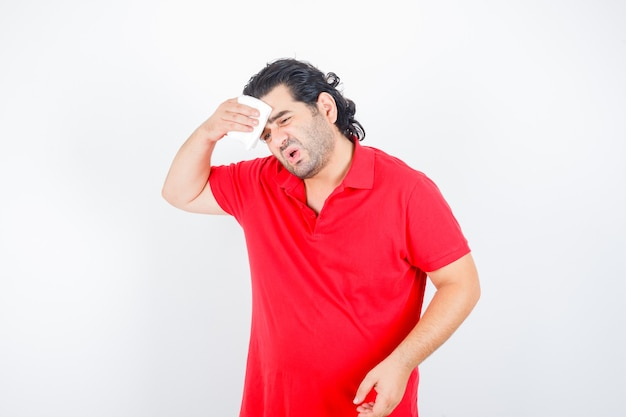 Middle aged man wiping sweat in red t-shirt and looking sick , front view.