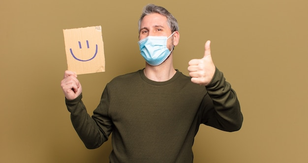 Middle aged man with medical mask and holding board with smiley