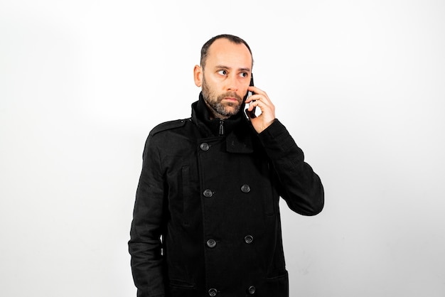 Middle-aged man with overcoat listens attentively to a conversation on his mobile phone