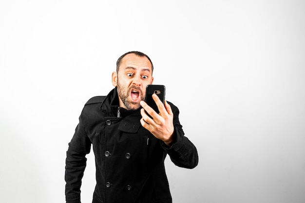 Middle-aged man with overcoat screams angrily at his mobile phone, isolated on white.