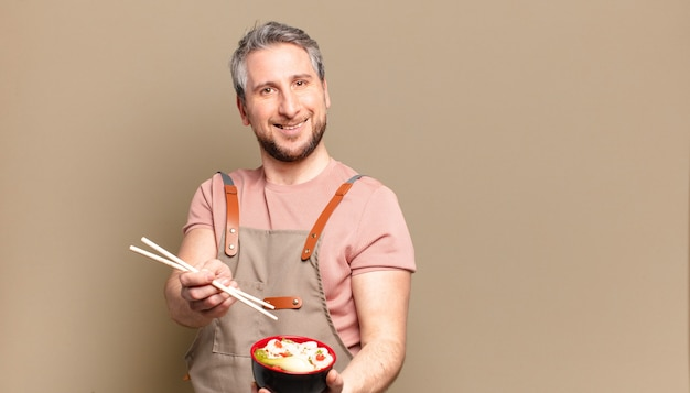 Middle aged man with a ramen bowl