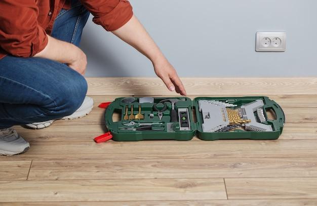 木の床に修理ツールのセットを持つ中年男性