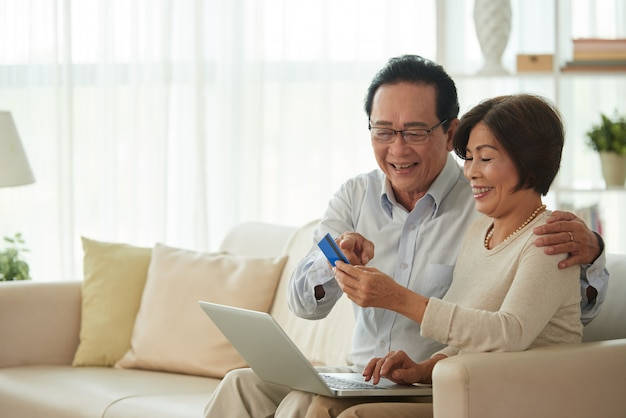Middle-aged man and |woman doing online shopping