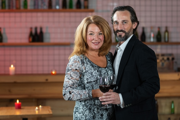 Middle-aged man and woman stand with raised glasses of wine and look into the camera
