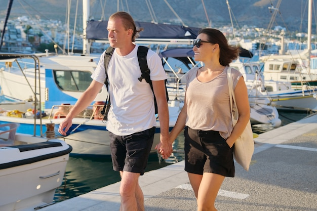 Middle-aged man and woman walking together holding hands. love, romance, communication mature people. background summer seascape, moored yachts in bay