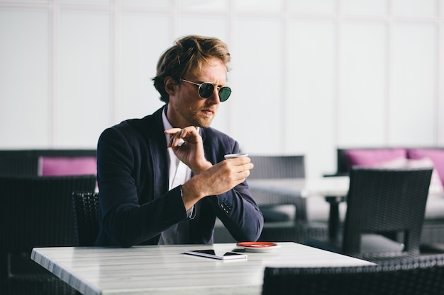 Middle aged manager businessman is sitting in a cafe with a cup of coffee