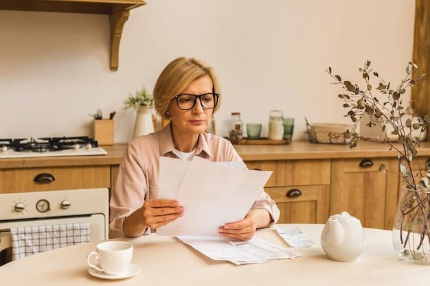 웹사이트에서 온라인 결제를 하고, 금융세 비용을 계산하고, 은행 계좌를 검토하기 위해 집에 종이 청구서나 편지를 들고 있는 중년의 중년 여성.