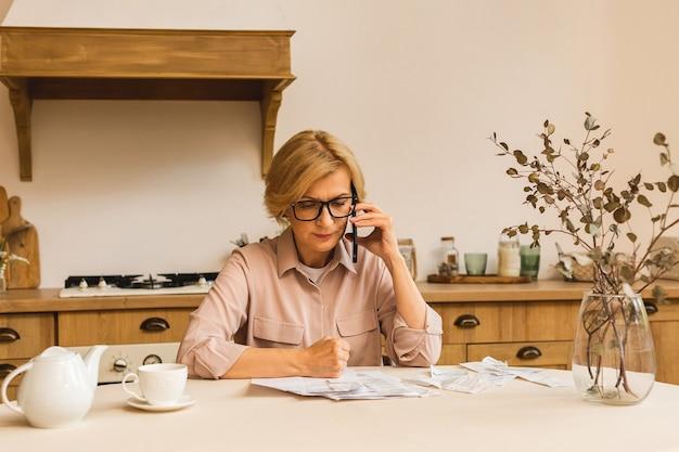 중년의 중년 여성은 휴대전화로 웹사이트에서 온라인 결제를 하고, 금융세 비용을 계산하고, 은행 계좌를 검토하기 위해 집에서 종이 청구서나 편지를 들고 있습니다.