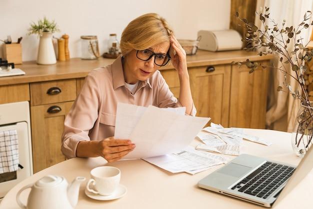웹사이트에서 온라인 결제를 하고, 금융세 비용을 계산하고, 은행 계좌를 검토하기 위해 집에서 노트북 컴퓨터를 사용하여 종이 청구서나 편지를 들고 있는 중년의 중년 여성.