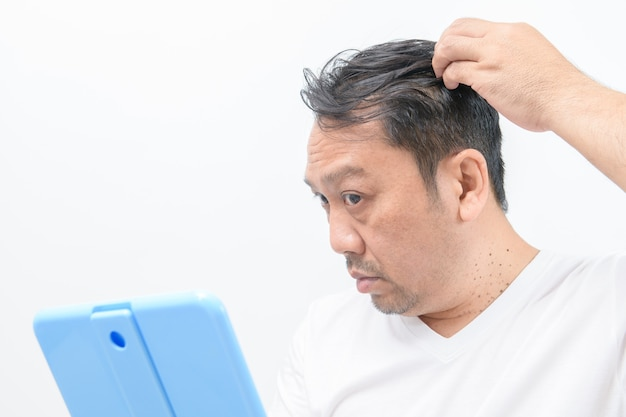 中年男性は脱毛や発毛を心配し、白い壁を孤立させ、