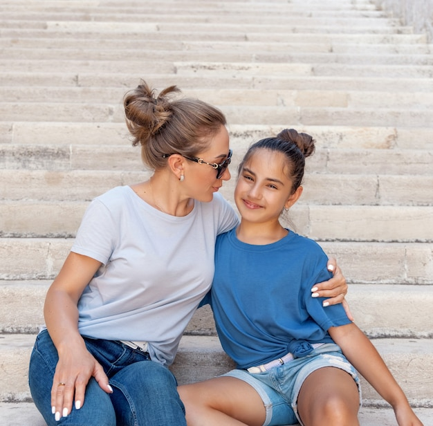 Middle-aged mother and her kid daughter sitting on stone stairs outdoor and embracing. loving family wearing blue t-shirts and jeans spending time together outdoors in summer, t-shirts mockup