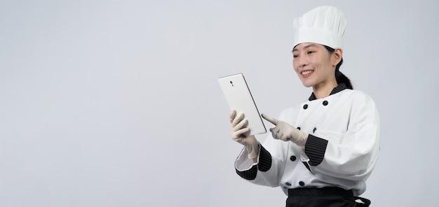 スマートフォンやデジタルタブレットを持っているアジアの女性シェフの中年で、オンラインショップやマーチャントアプリケーションから注文を受けました。
