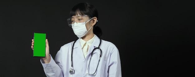 何かを伝えるために携帯電話の画面を表示しているアジアの女性医師の中年