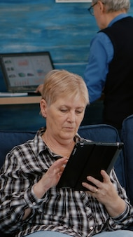 Middle aged old woman relaxing holding tablet reading e book