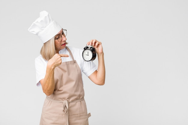 Middle-aged pretty baker woman holding an alarm clock