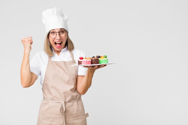 Middle-aged pretty baker woman with cakes against wall
