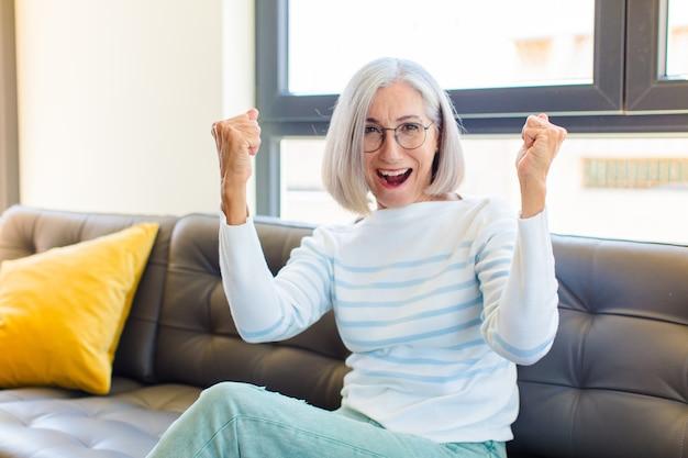 Симпатичная женщина средних лет празднует невероятный успех как победительница, выглядит взволнованной и счастливой, говоря: «бери!»