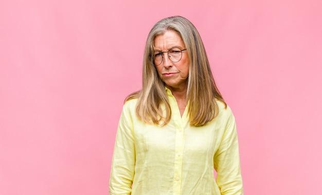Симпатичная женщина средних лет, потрясенная, изумленная и удивленная, с рукой на груди и открытым ртом спрашивает, кто, я?