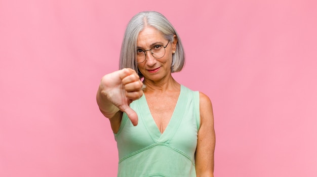 Красивая женщина средних лет улыбается и выглядит счастливой, беззаботной и позитивной, жестикулируя победу или мир одной рукой