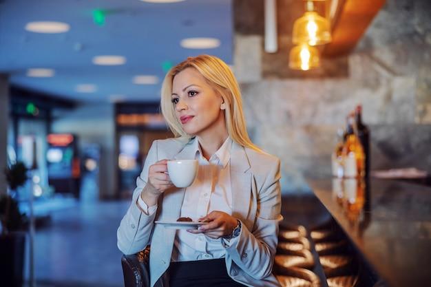 ホテルのカフェに座って白いコーヒーを持っている中年のプロの金髪。彼女は誰かを待っています。楽しみ、コーヒーブレイク