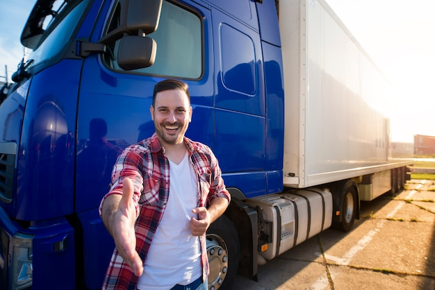 트럭 앞에 서서 신입 사원에게 악수를주는 중년의 전문 트럭 운전사.