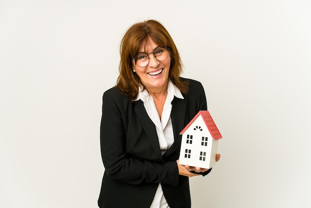 Middle aged real estate agent holding a house model isolated laughing and having fun.