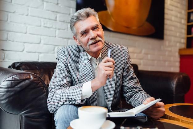 トレンディなスーツを着た中年の年配の男性は、モダンなカフェショップでコーヒーと本を飲みながら素敵な週末を過ごします。