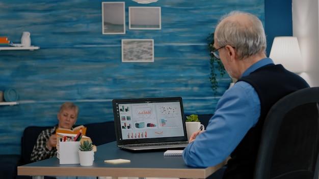 ビジネスグラフを分析する中年の年配の男性