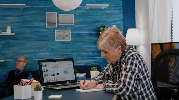 中年の年配の女性eラーニングオンラインコンセプトノートパソコンでビジネスグラフチャートを見て...