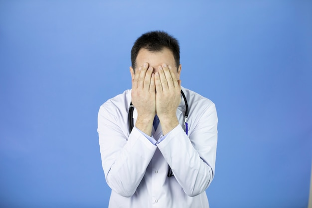 Middle-aged shocked doctor covering face with hands because of mistake, fatigue