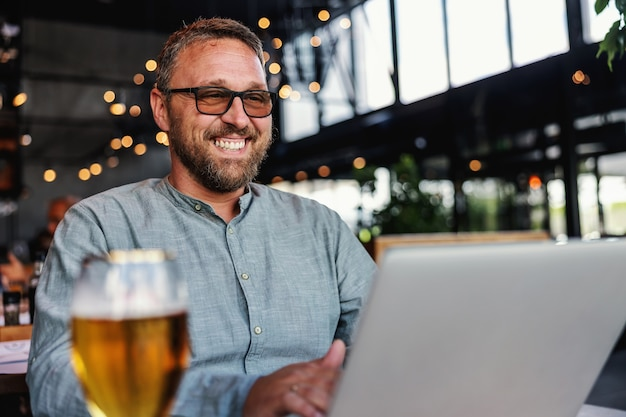 Middle aged smiling bearded man with eyeglasses sitting in his bar, using laptop and having a glass of fresh cold light beer.