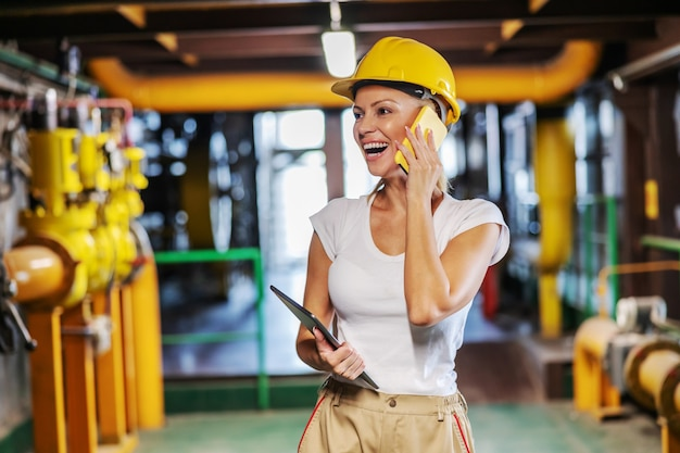 Улыбающаяся женщина-руководитель средних лет в рабочей форме со шлемом на голове держит планшет и разговаривает по телефону, стоя на теплоцентрали.