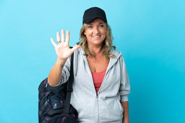 Спортивная женщина средних лет на изолированном фоне, считая пять пальцами