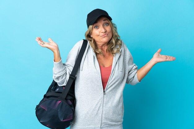 Спортивная женщина средних лет на изолированном фоне, сомневаясь, поднимая руки