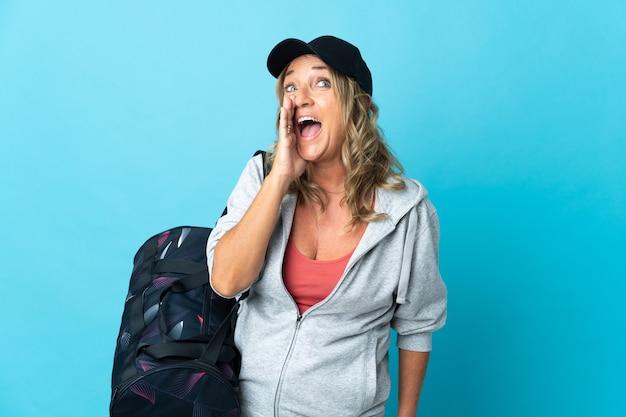 Спортивная женщина средних лет над изолированным криком с широко открытым ртом