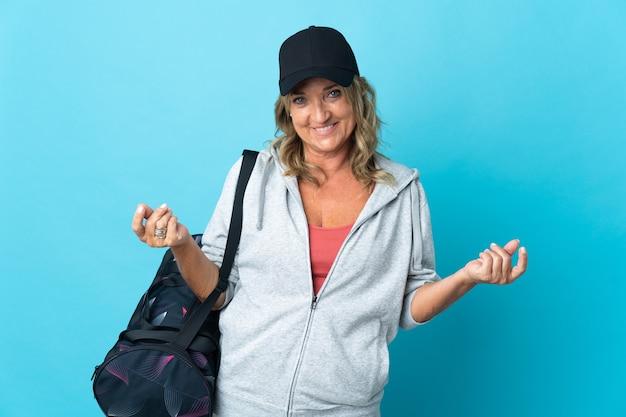 Спортивная женщина средних лет над изолированной стеной делает денежный жест