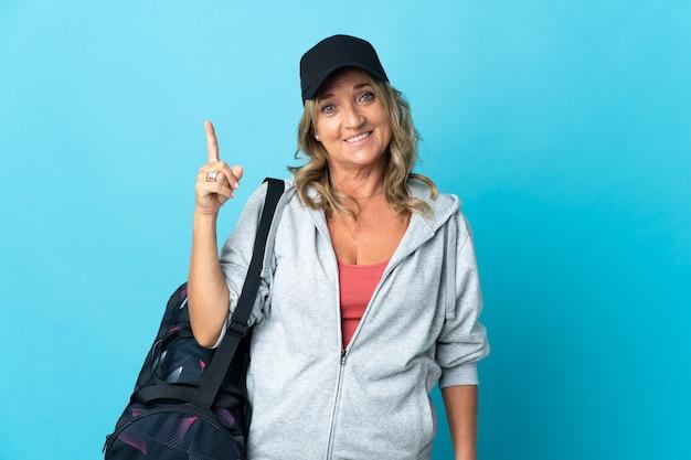 Спортивная женщина средних лет над изолированной стеной показывает и поднимает палец в знак лучших
