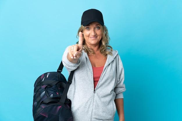 Спортивная женщина средних лет над изолированной стеной показывает и поднимает палец