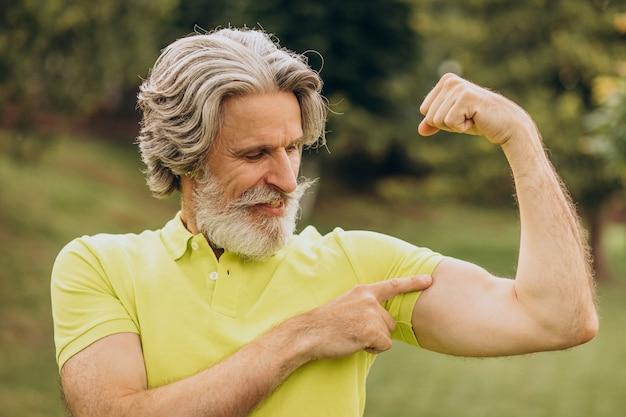 彼の上腕二頭筋を指している中年のスポーツマン