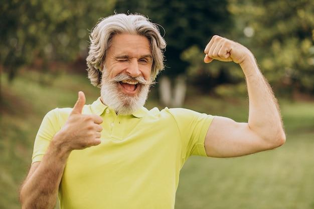 Спортсмен средних лет, указывая на его бицепс