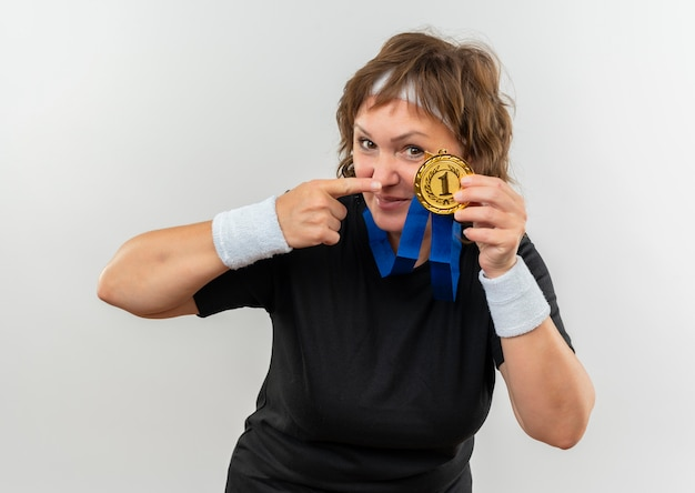 Middle aged sporty woman in black t-shirt with headband and gold medal around her neck pointing with finger to it smiling confident standing over white wall