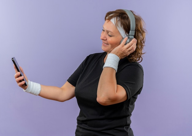 Donna sportiva di mezza età in maglietta nera con archetto e cuffie guardando lo schermo della sua musica di ricerca mobile in piedi sopra la parete blu