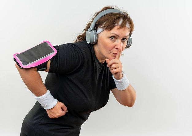 Middle aged sporty woman in black t-shirt with headband and headphones working out making silence gesture with finger on lips standing over white wall