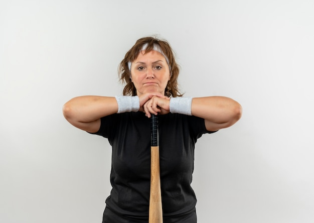 Middle aged sporty woman in black t-shirt with headband holding baseball bat displeased standing over white wall